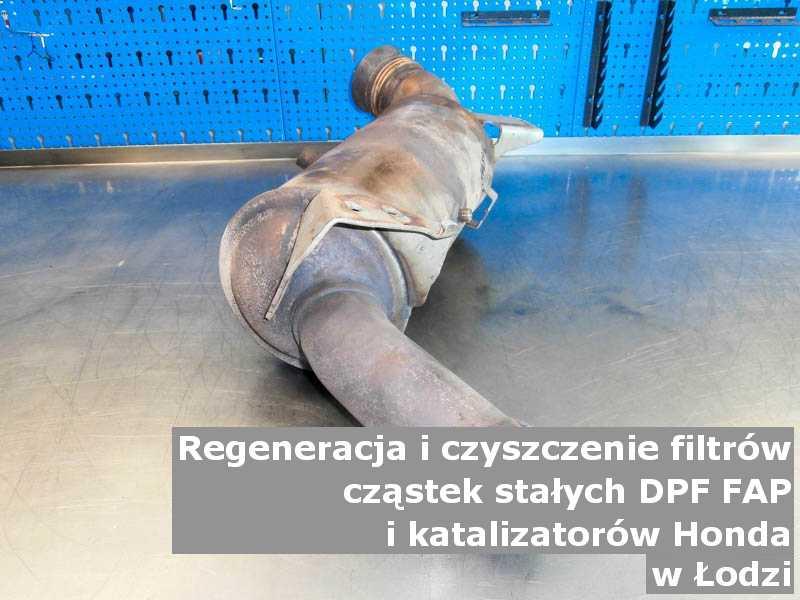 Wypalony z sadzy filtr FAP marki Honda, w pracowni regeneracji na stole, w Łodzi.