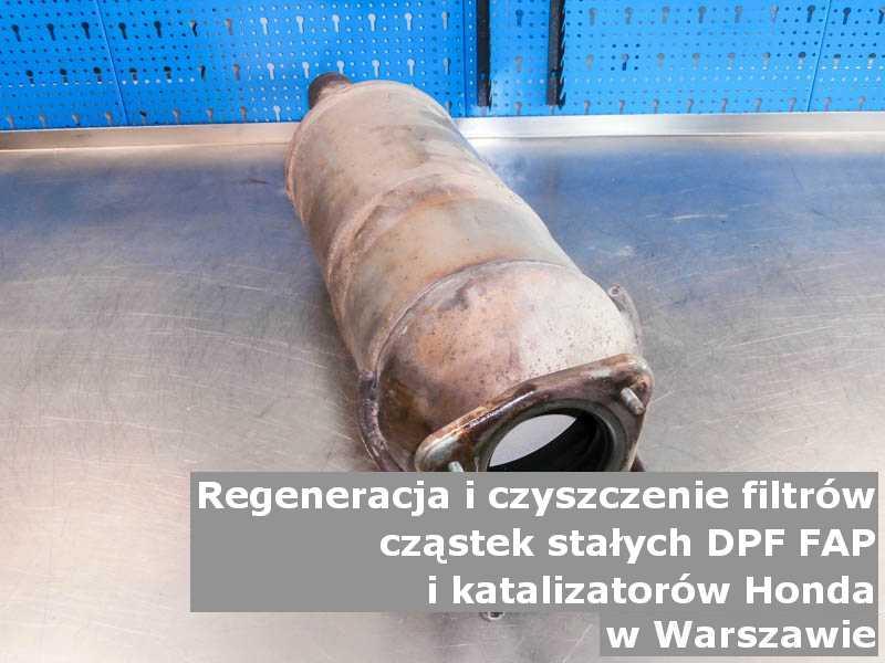Wypalony filtr cząstek stałych DPF marki Honda, na stole w pracowni regeneracji, w Warszawie.
