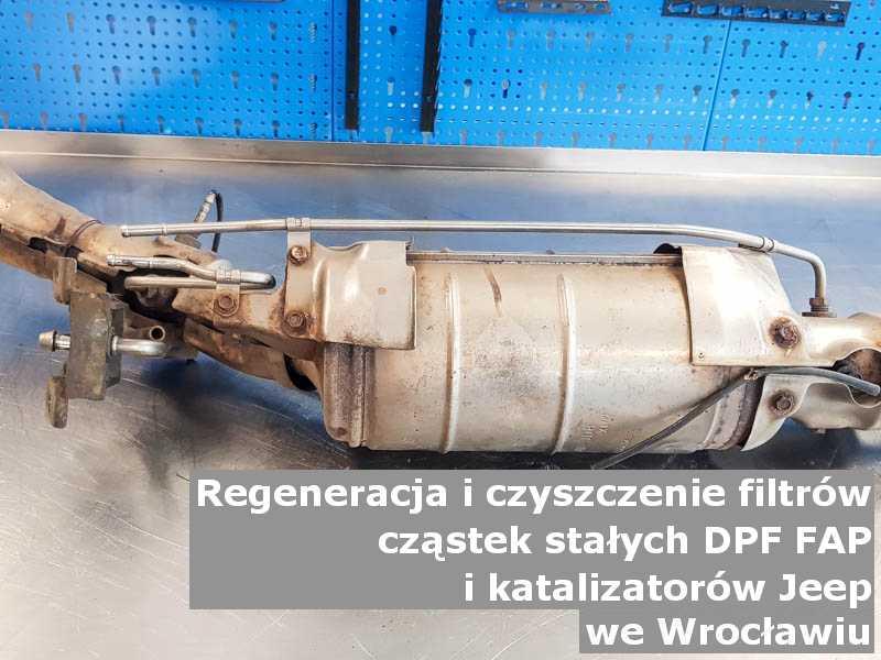Wypalony z sadzy katalizator SCR marki Jeep, w pracowni regeneracji na stole, w Wrocławiu.