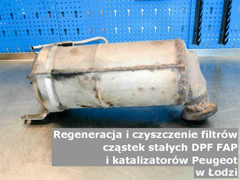 Naprawiany filtr FAP marki Peugeot, w pracowni regeneracji na stole, w Łodzi.